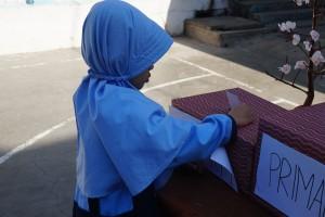 Siswi memasukkan kertas suaranya ke dalam kotak suara