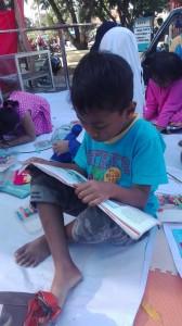 seorang anak terlihat serius membaca buku bacaan yang telah disediakan